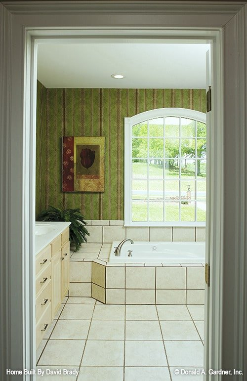 The primary bathroom is equipped with sink vanity and a drop-in bathtub fixed under the arched window.