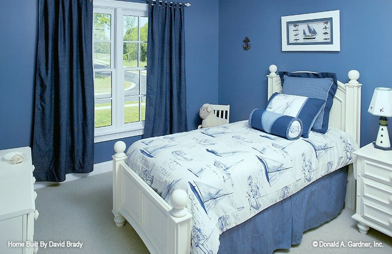 This bedroom showcases white furnishings and blue walls adorned with a white framed artwork.