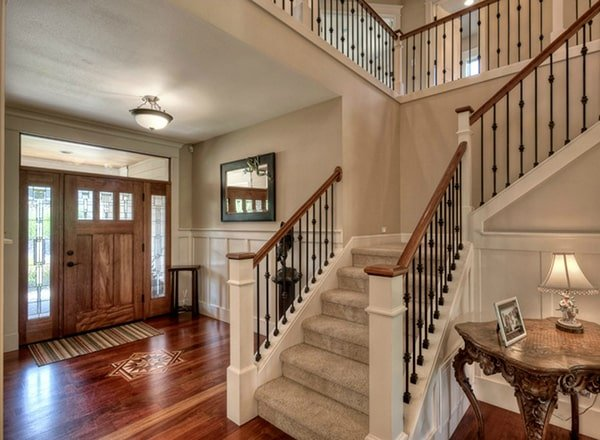 The foyer has a wooden entry door, a carpeted staircase, and a carved wood center table.