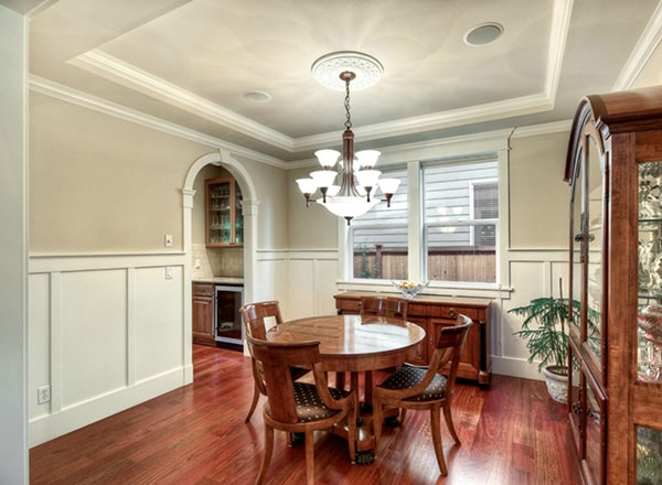 Formal dining room with wooden display cabinet, buffet bar, and a round dining set well-lit by a glass chandelier.