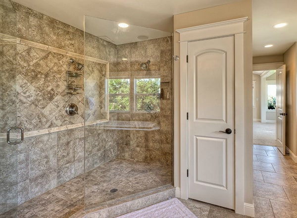 The primary bathroom features a walk-in shower enclosed in frameless glass panels.