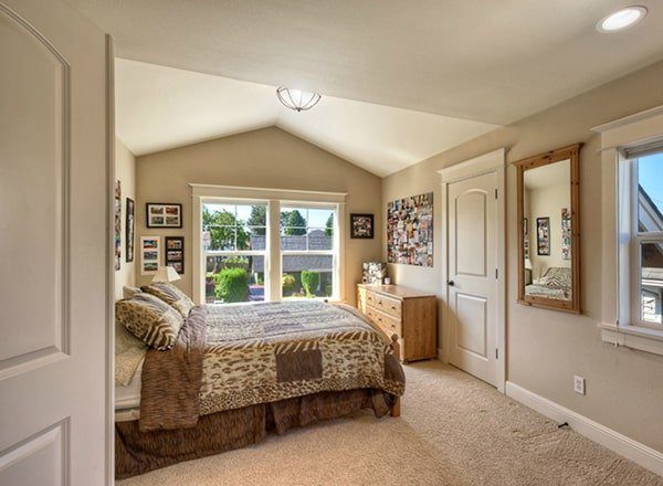 This bedroom has a skirted bed, vaulted ceiling, and beige walls adorned with photos and a mirror.
