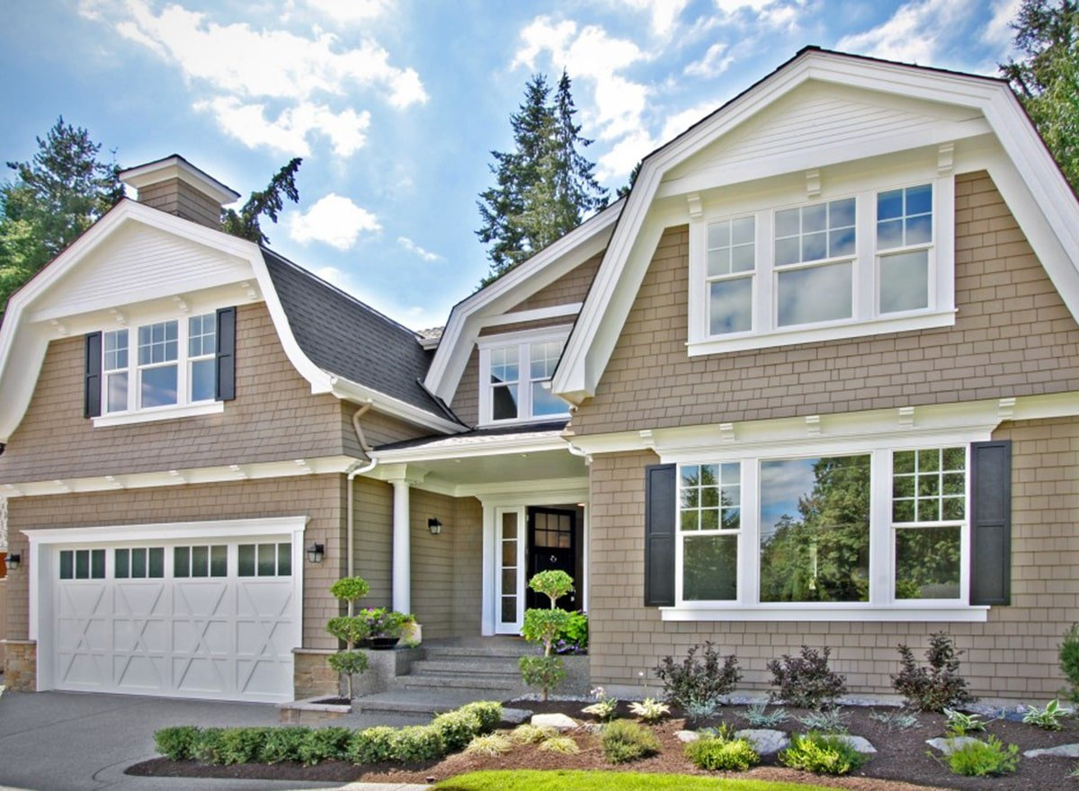 This is a close look at the front of the shingle-style home that has gambrel roofs, light beige exterior walls, white frames and accents and lush landscaping that has a concrete driveway, a concrete walkway, shrubs and planters.