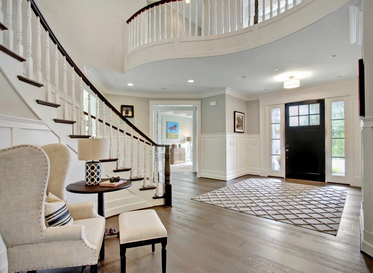 The foyer showcases a black front door and a large patterned rug that lays on the natural hardwood flooring.