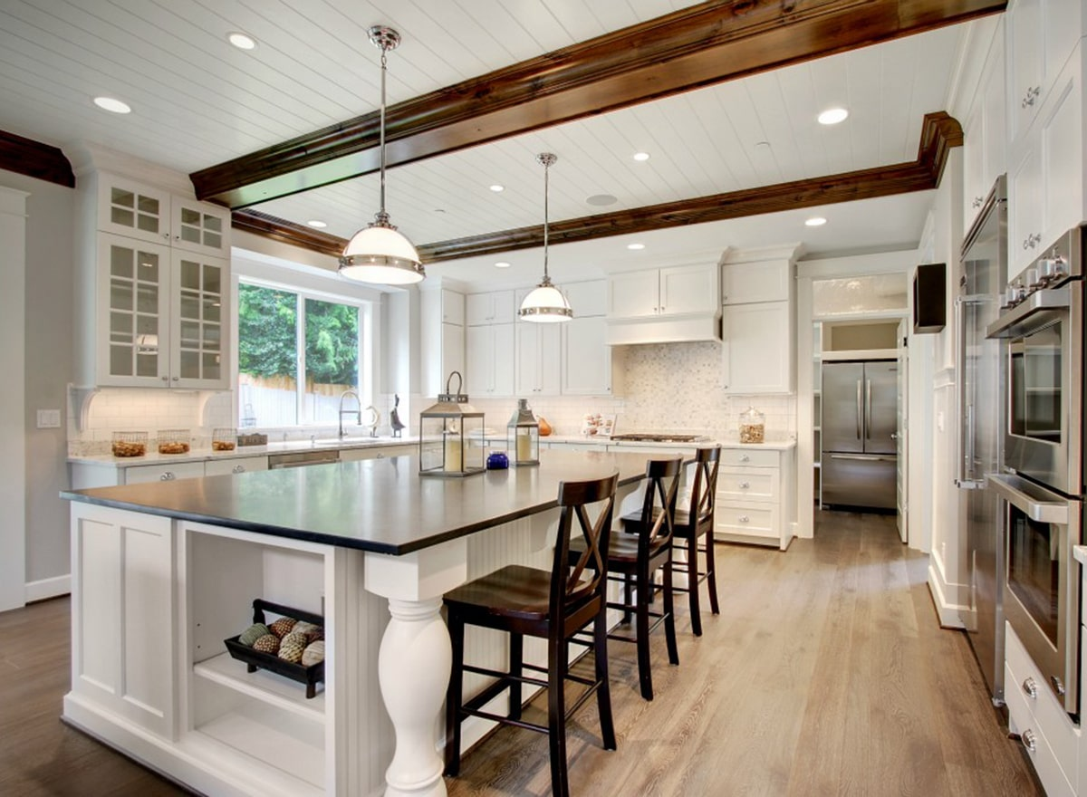 Kitchen with white cabinets, natural hardwood flooring, and a white shiplap ceiling lined with dark wood beams.