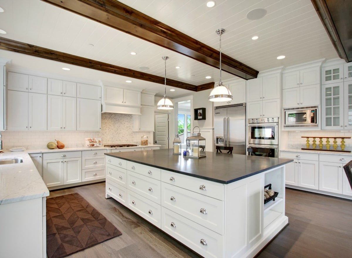 The kitchen is dominated by the pure white shaker cabinets lining the walls and the matching shaker drawers on the large kitchen island contrasted by its black counter. These are then complemented by the beige backsplash and exposed wooden beams of the ceiling.