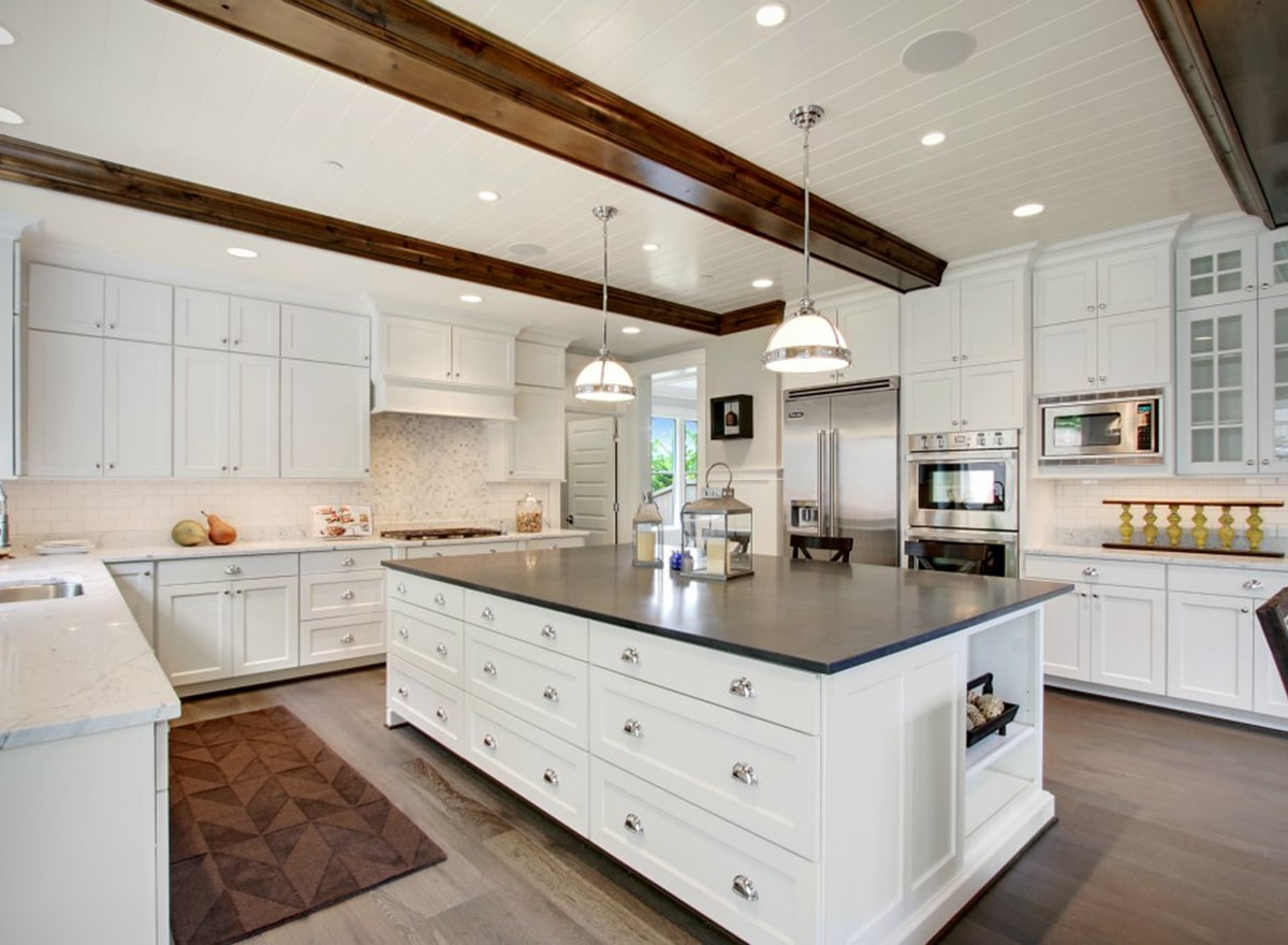 The kitchen is equipped with white marble countertops, stainless steel appliances, and an immense island fitted with built-in shelves and drawers.