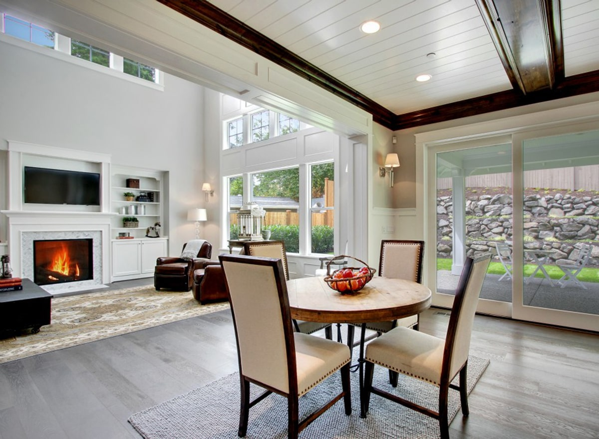Breakfast nook with a round table and beige upholstered chairs sitting on a gray area rug.