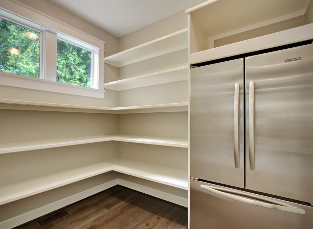The walk-in pantry is filled with white built-in shelves and a two-door fridge.
