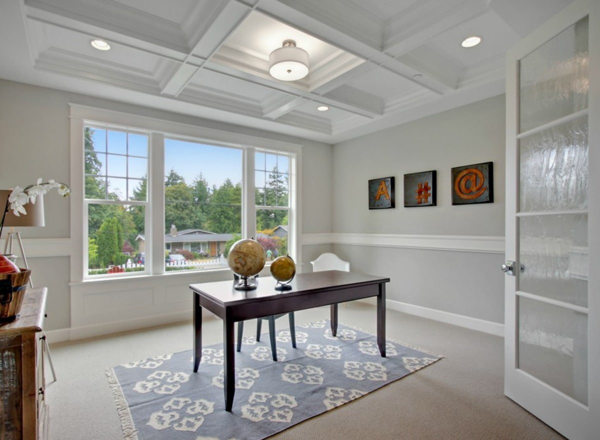 Home office with coffered ceiling, three-panel windows, and light gray walls adorned with black artworks and white moldings.