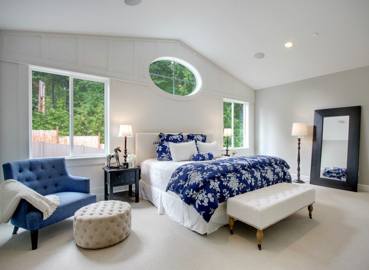 Primary bedroom with white skirted bed, comfy tufted seats, and a full-length mirror.
