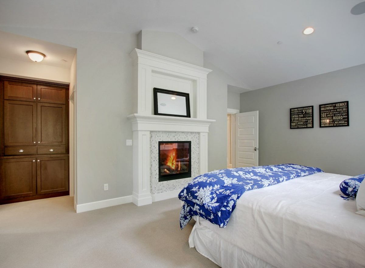 There's also a glass-enclosed fireplace in front topped with a black framed mirror.