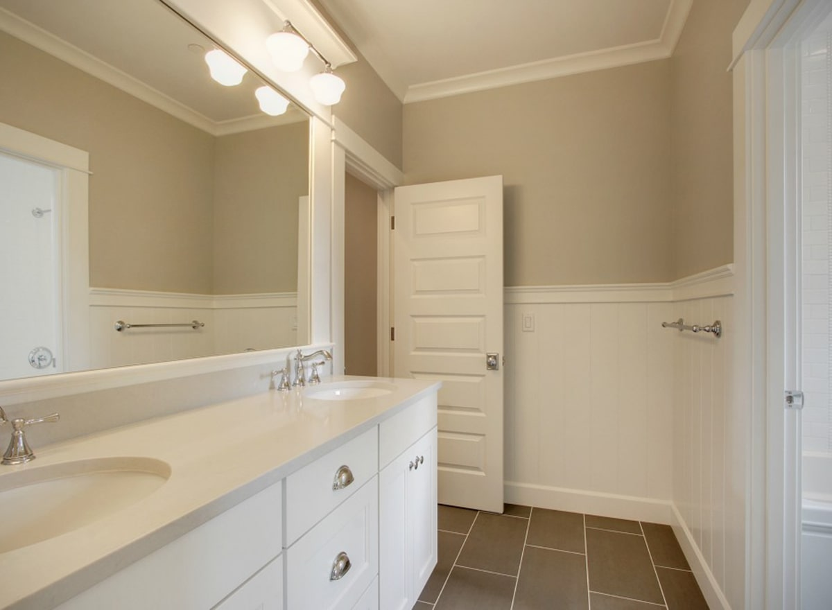 This is a close look at the primary bathroom with white modern cabinets and drawers on its two-sink vanity topped with a large mirror and sets of wall sconces across from the shower area. These are then complemented by the white wainscoting and gray flooring tiles.