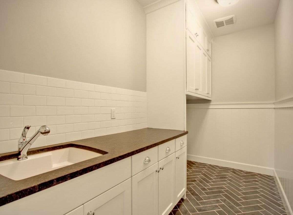 Utility room with herringbone tiled flooring, white subway tile backsplash, modular cabinets, and an undermount sink.