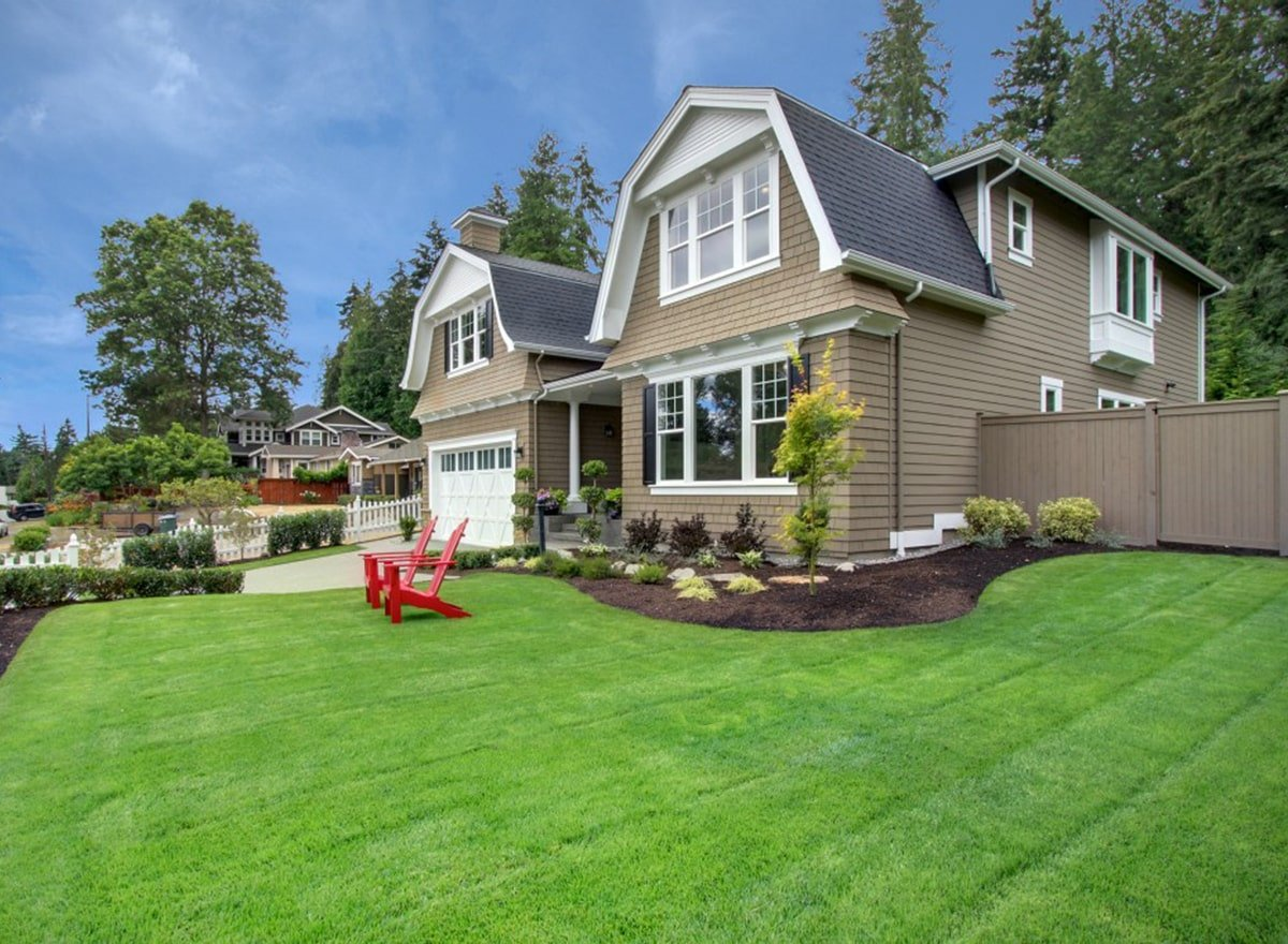 This is a close look at the front lawn of the house that has gambrel roofs and beige exterior walls. These are complemented by the landscaping of grass lawns, a concrete driveway, and lines of well-manicured shrubs.