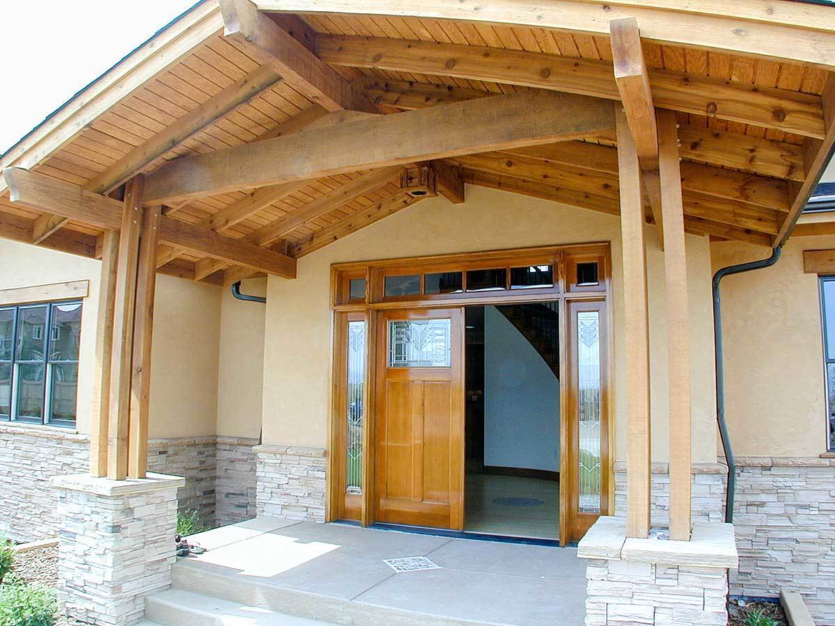 Covered front porch showcasing a wooden french entry door, tapered columns, and a wood-beamed cathedral ceiling.