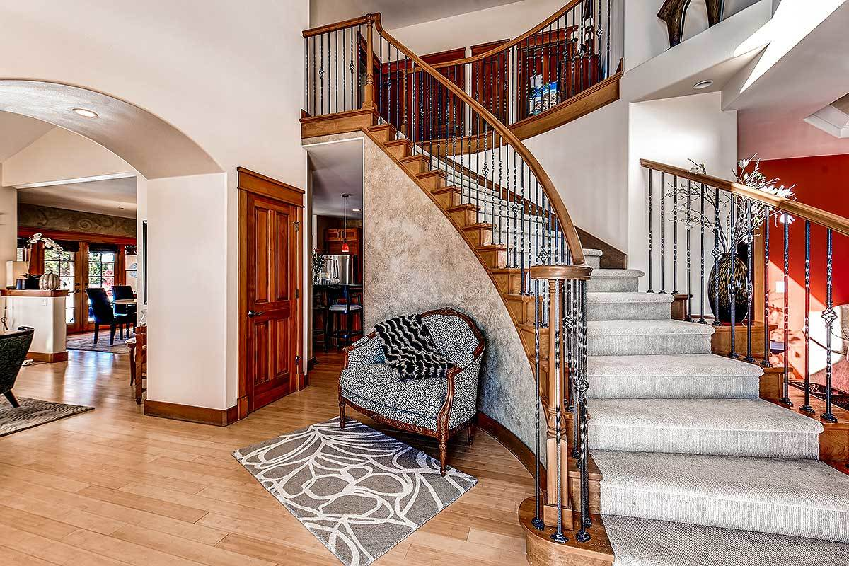 Foyer with an intricate winding staircase complemented with a round back chair and a gray printed rug.