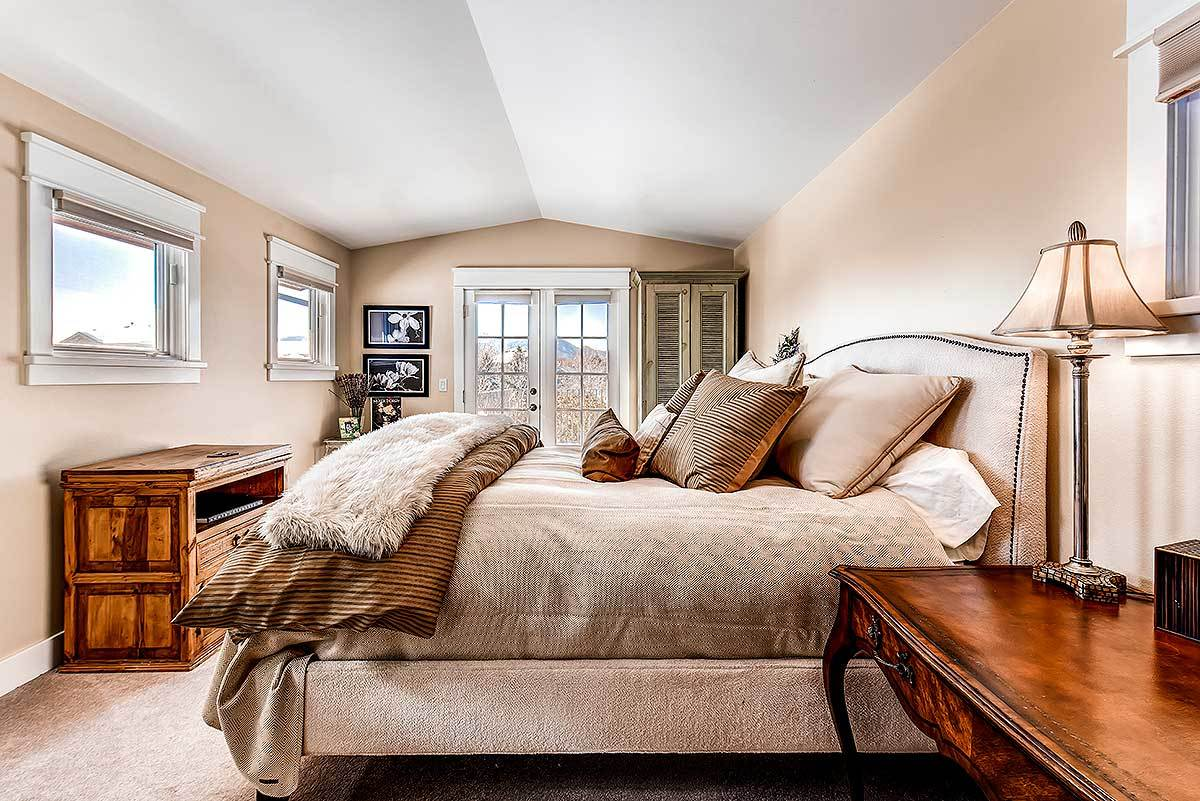 This bedroom has a vaulted ceiling, french door, and carpet flooring that matches the beige upholstered bed.