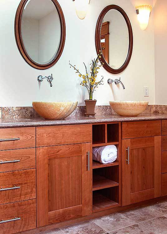 A pair of oval mirrors hang above the wooden vanity with dual vessel sinks and a granite countertop.