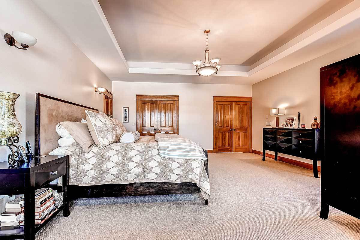 The primary bedroom has dark wood furnishings, beige walls, and a tray ceiling mounted with a warm glass chandelier.