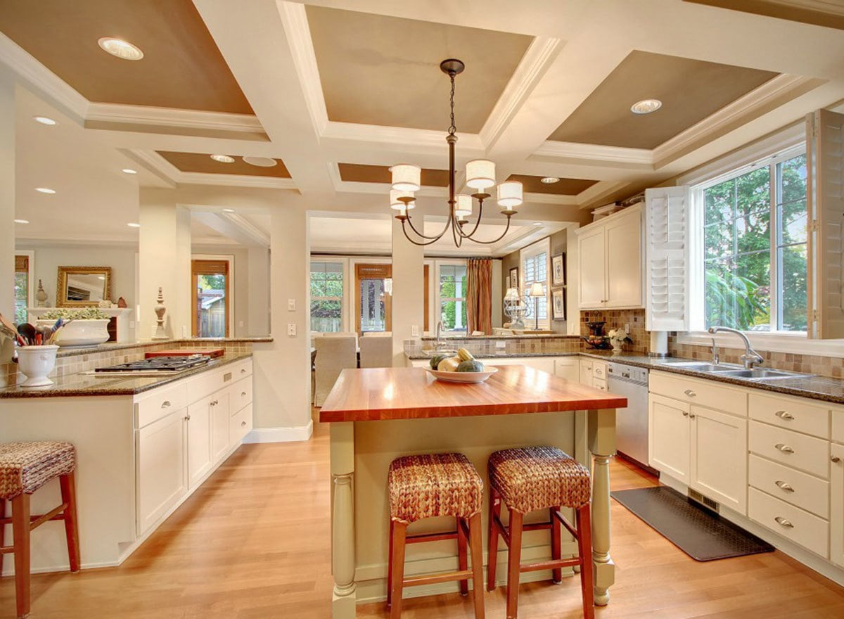 A decorative coffered ceiling mounted with a wrought iron chandelier and recessed lights crowned the kitchen.