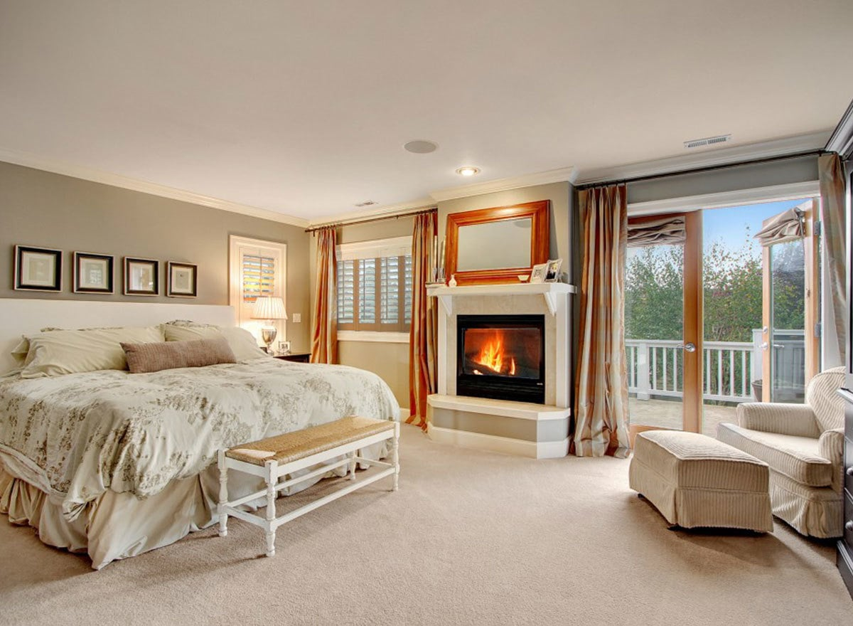 The primary bedroom offers a warm fireplace, beige carpet flooring, and a private deck accessible via the french door next to the skirted lounge chair.