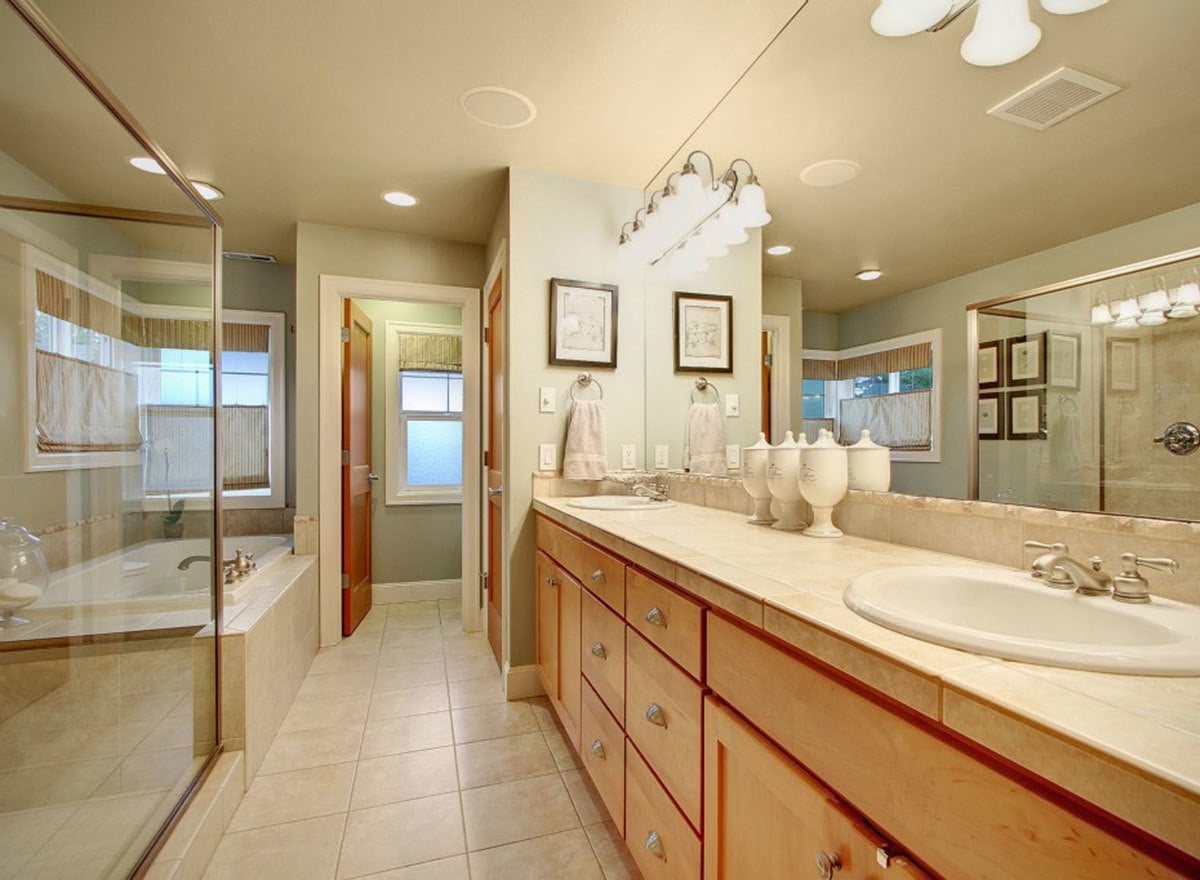 Primary bathroom with a deep soaking tub, a walk-in shower, and a dual sink vanity well-lit by glass sconces.