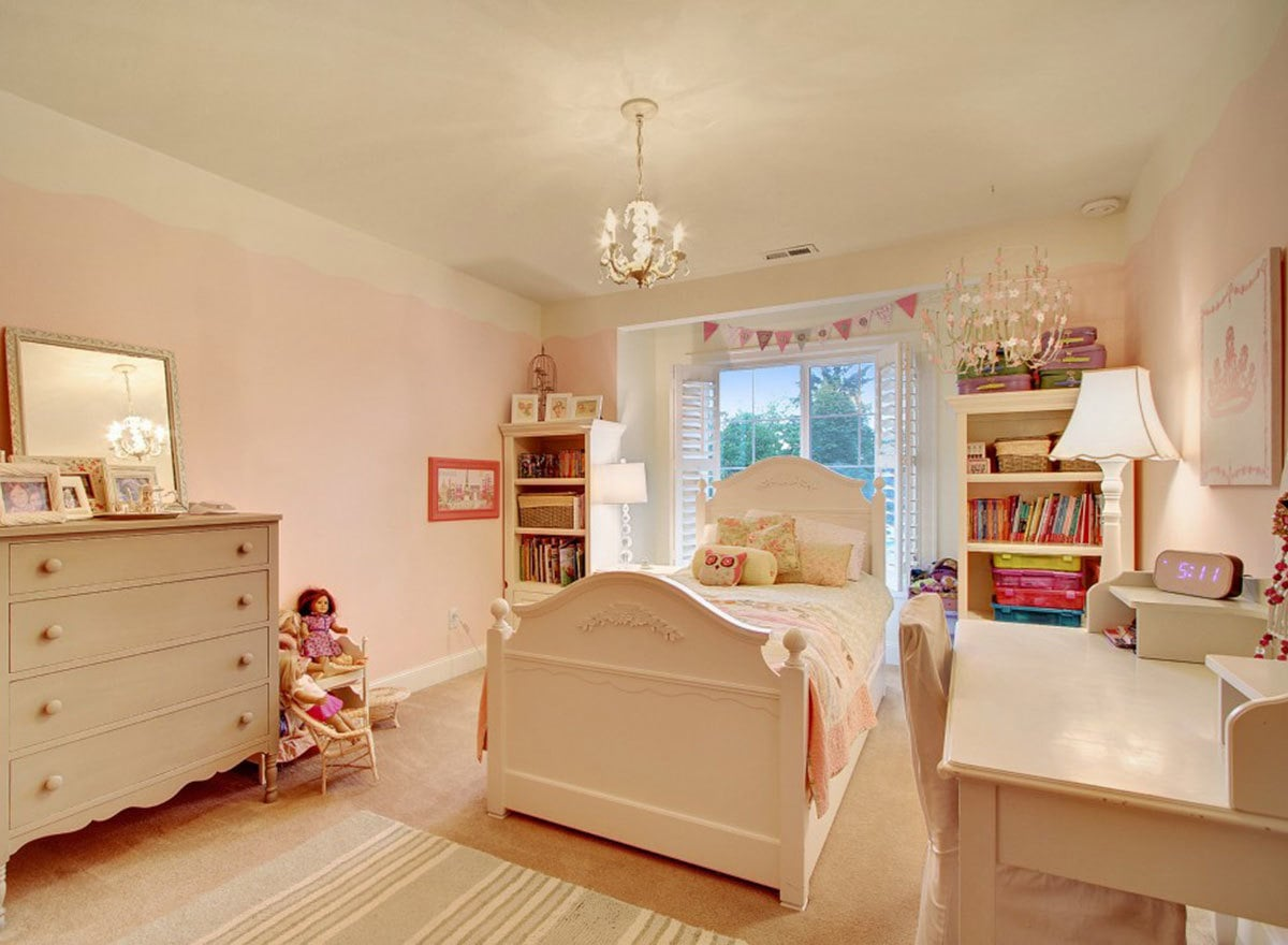 Kid's bedroom with light pink walls, white furnishings, and a tall window enclosed in louvered shutters.