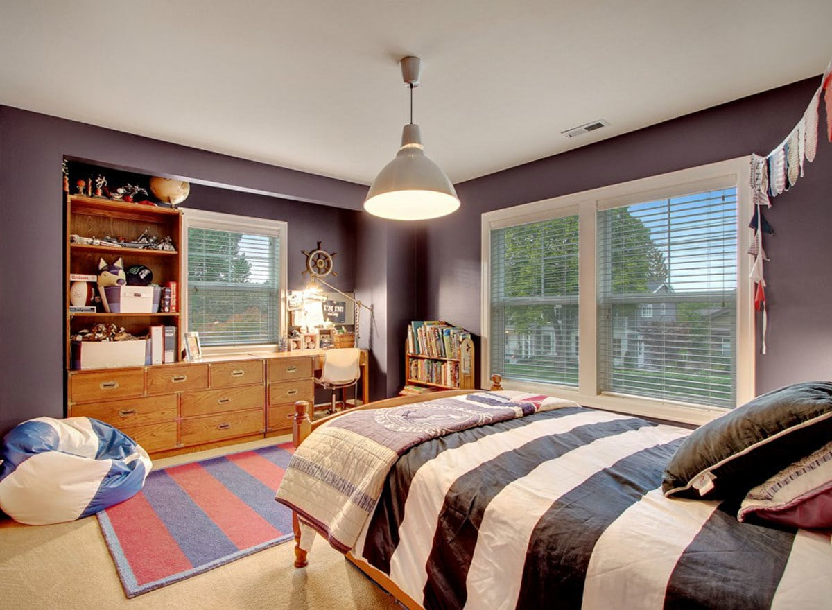 Another bedroom with a cozy wooden bed, striped rug, and built-in cabinet fitted on the purple inset wall.