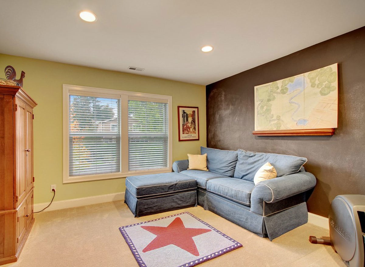 Bonus room with a blue skirted sofa, wooden cabinet, and a star printed rug that lays on the beige carpet flooring.