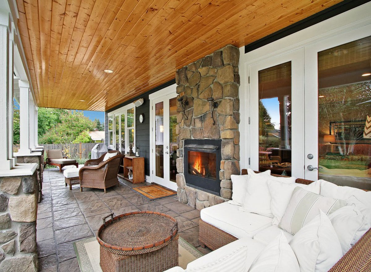 The back porch offers cushioned wicker seats, matching ottomans, and a stone fireplace that matches the tapered columns.