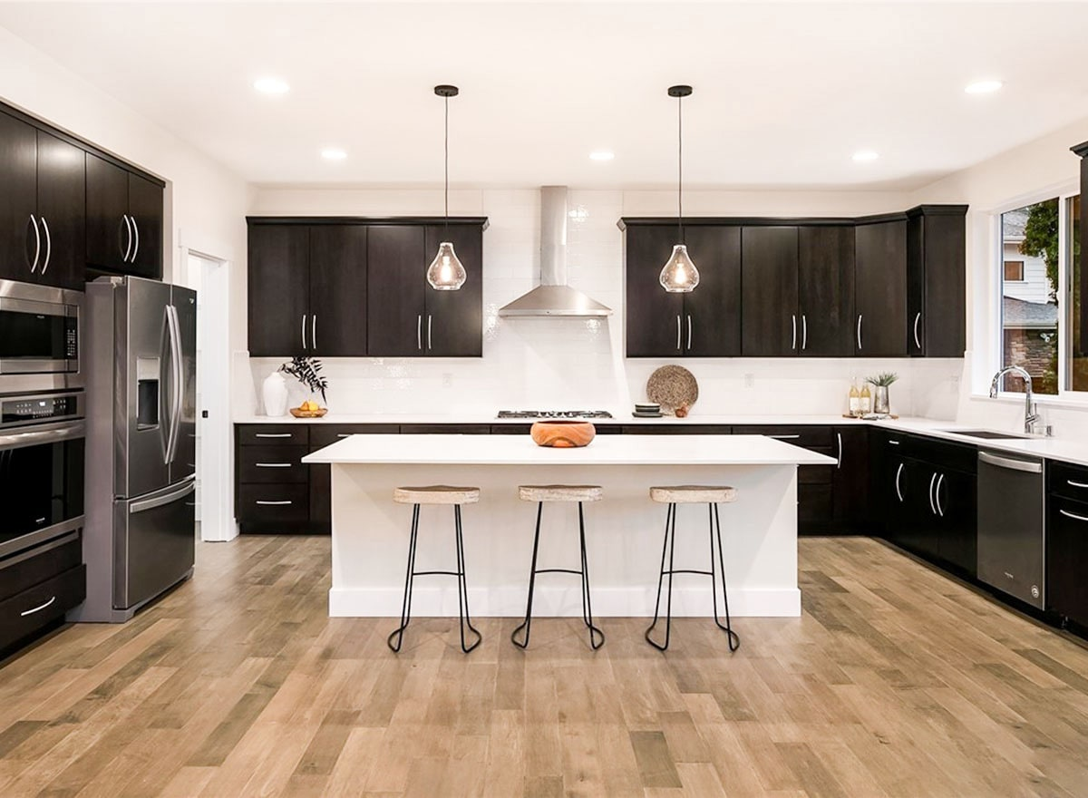 The kitchen is equipped with dark wood cabinetry, stainless steel appliances, quartz countertop, and a white breakfast island.
