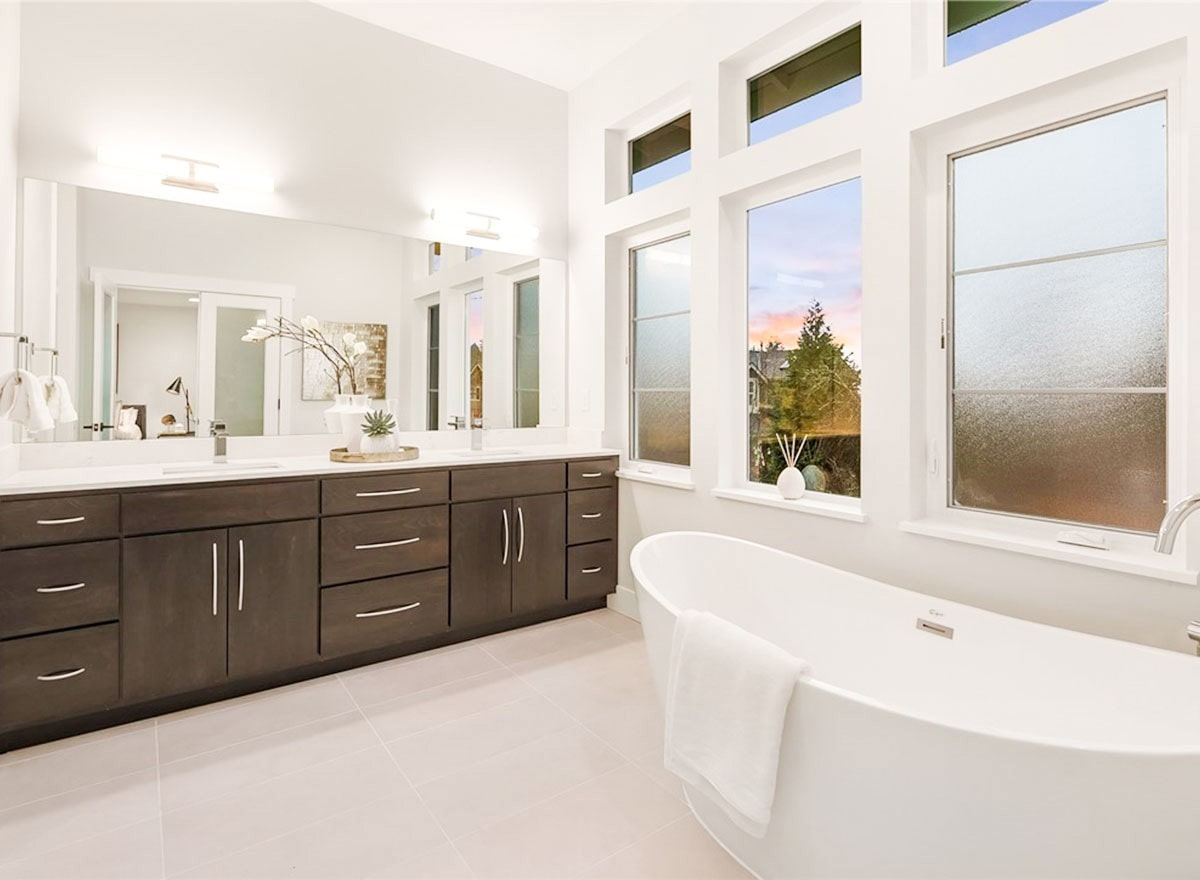 The primary bath has a freestanding tub and a dual sink vanity paired with a rectangular frameless mirror.