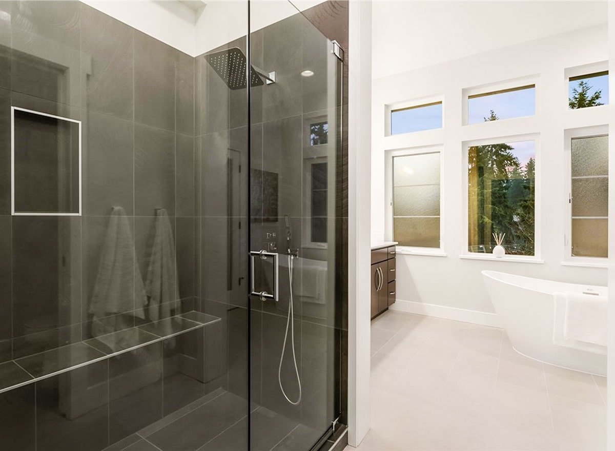 The walk-in shower showcases an inset shelf, chrome fixtures, and a tiled bench.