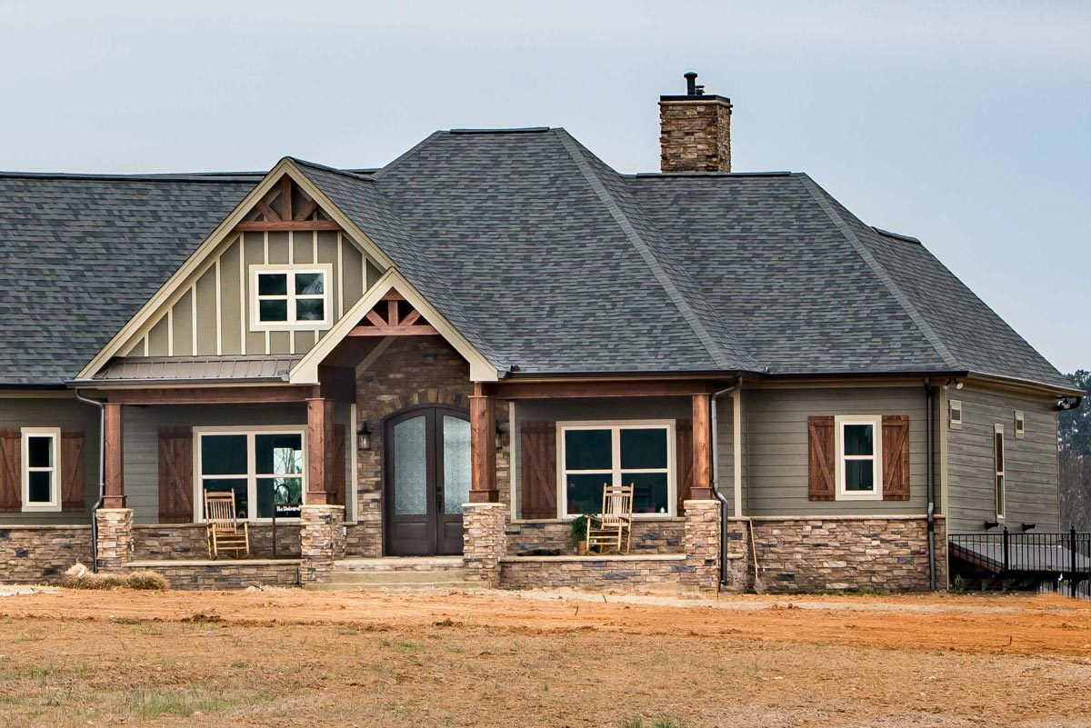 Home facade showing the hipped and gable roofs, stone chimney, and a covered front porch.