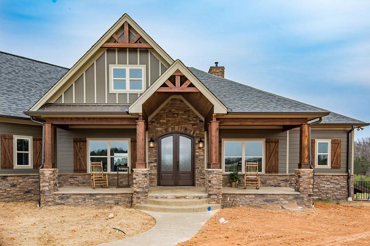 The covered front porch has an arched french entry door, brick accents, tapered columns, and a concrete stoop.