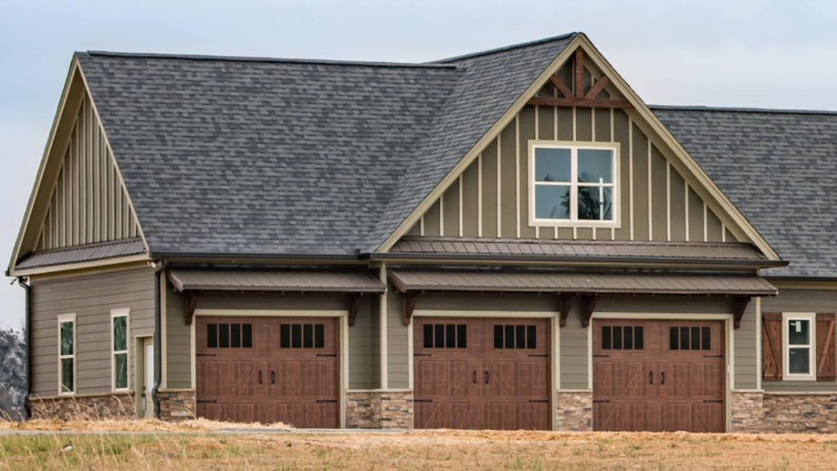An oversized garage with taupe exterior siding and three sets of wooden double doors.