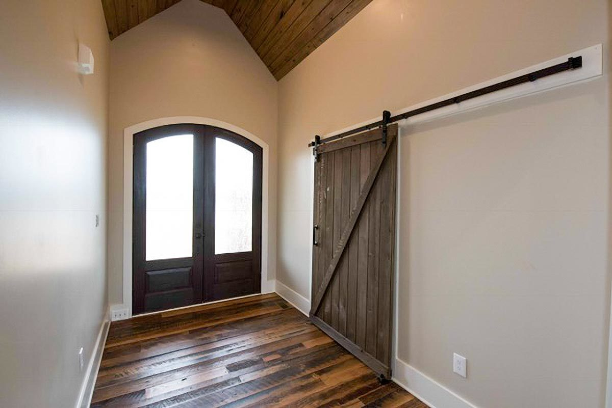 The foyer has beige walls and a cathedral ceiling clad in wood planks. A barn door on the side leads to the formal dining room.