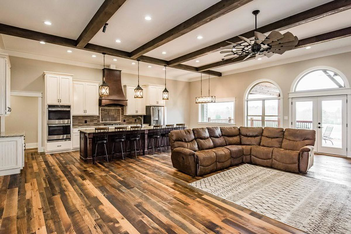 Living room with leather L-shaped sectional, a patterned rug, and a wrought iron fan that hangs from the beamed ceiling.
