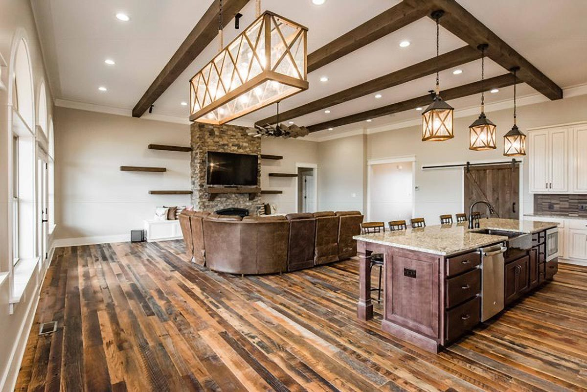 An open layout view showing the living room, kitchen, and an empty breakfast nook brightened by a brass chandelier.