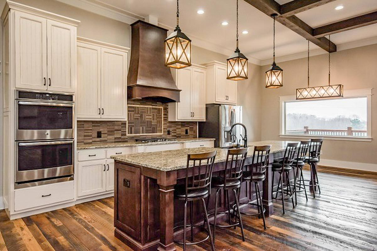 Glass pendants, recessed ceiling lights, and natural light streaming in from the picture window illuminate the kitchen.