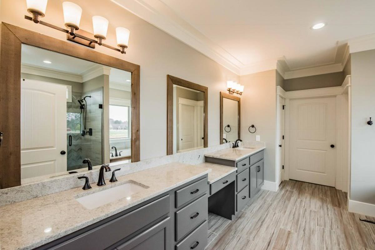 Primary bathroom with a dual sink vanity paired with wooden framed windows.