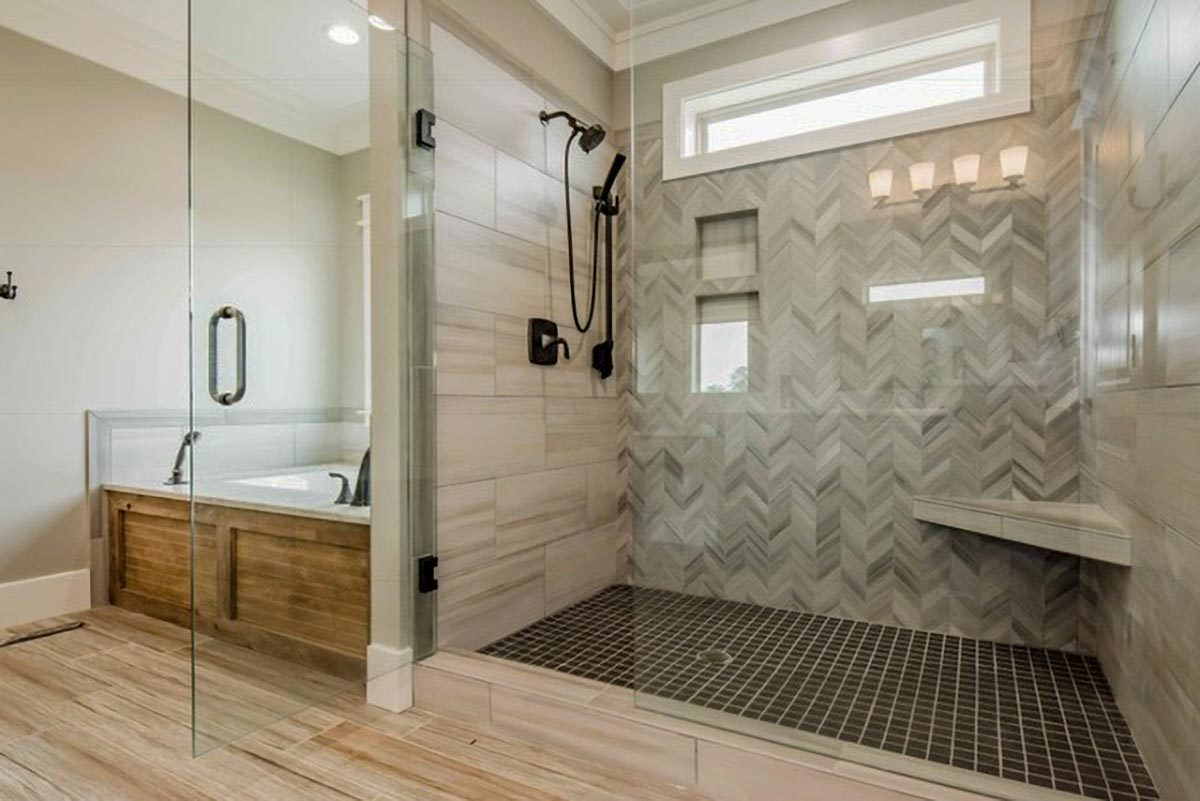 Deep soaking tub and a walk-in shower accentuated with herringbone tiles backsplash complete the primary bathroom.