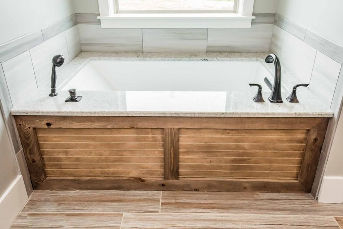 A closer look at the drop-in bathtub with wrought iron fixtures and a wood surround.