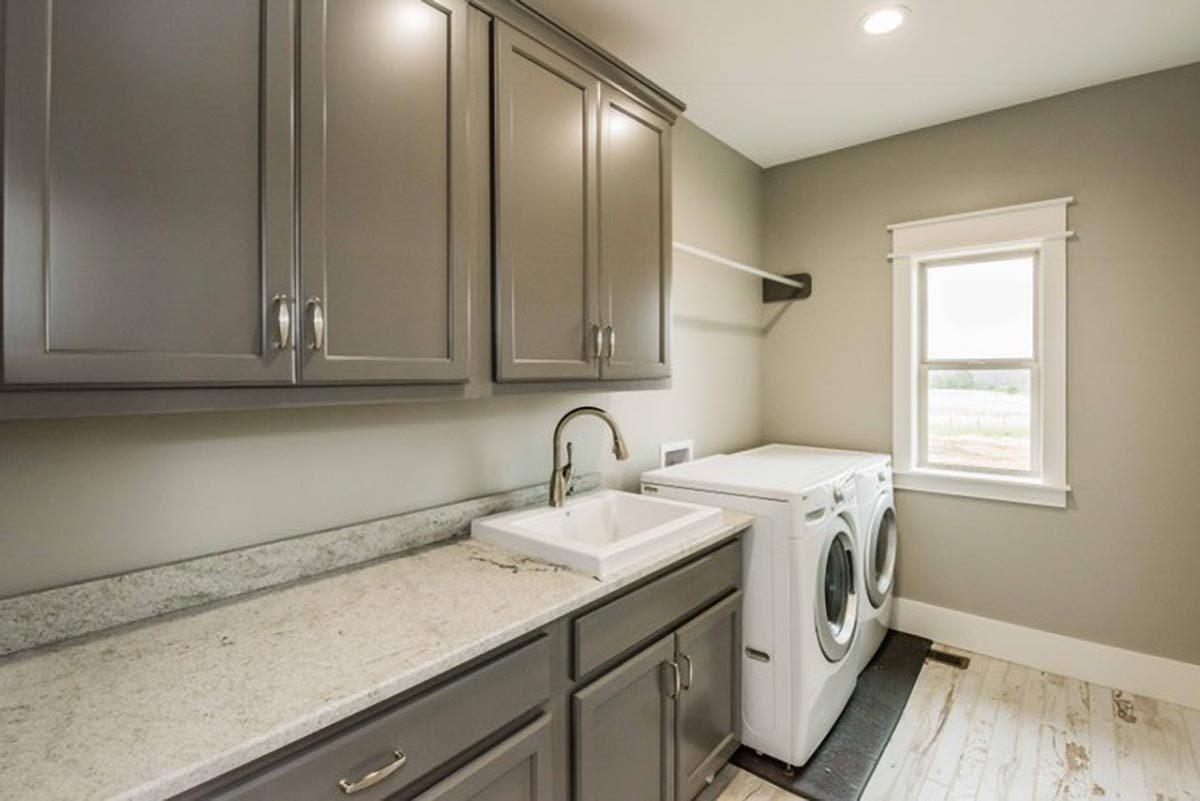 The utility is filled with white front-load appliances, gray cabinets, and a porcelain sink.