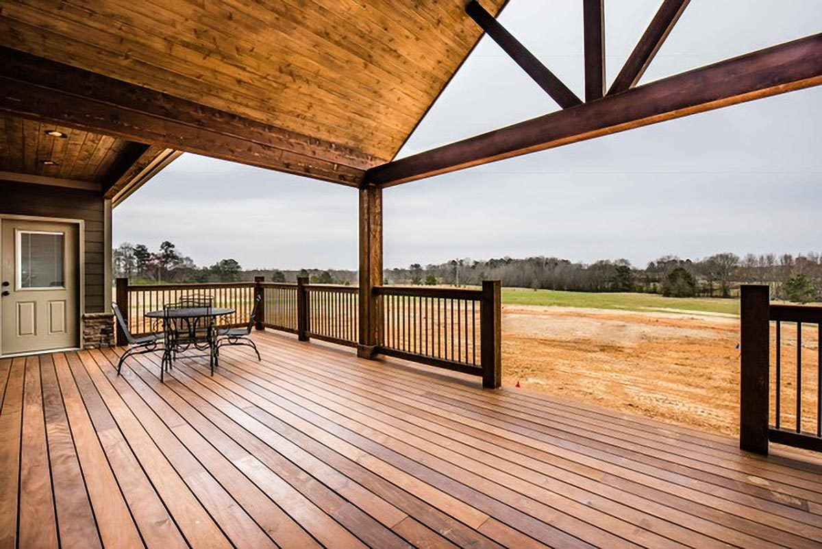 A spacious covered deck with vaulted ceiling and wide plank flooring overlooking an expansive view.