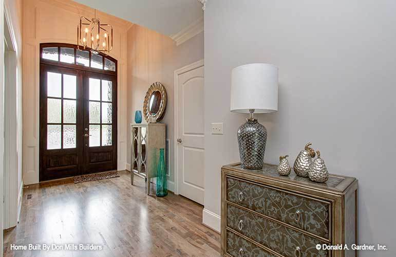 The foyer has a wooden french door, candle chandelier, and a stylish console table topped with a round mirror and transparent blue vase.