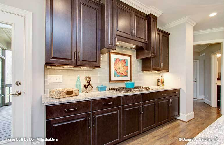 Kitchen with dark wood cabinetry, granite countertops, and a built-in cooktop adorned with floral artwork.