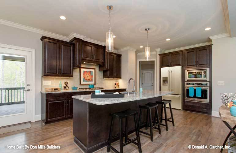 White two-door fridge, double wall oven, and a granite top island complete the kitchen.