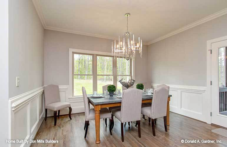 The dining area offers a candle chandelier and a rectangular dining table surrounded with beige upholstered chairs.